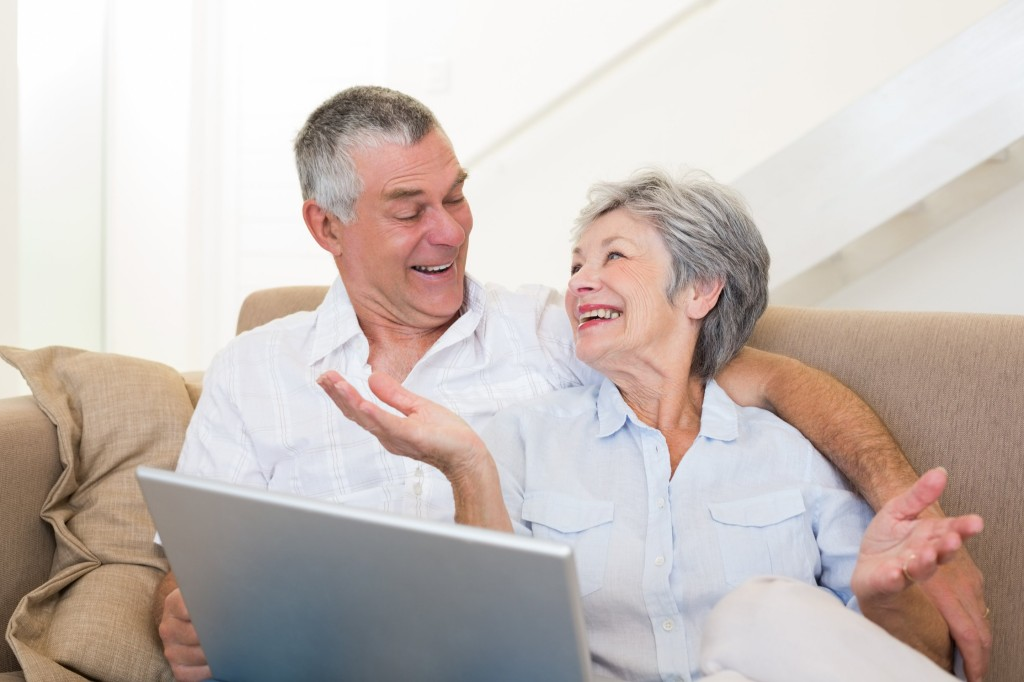 Loving senior couple with laptop on sofa