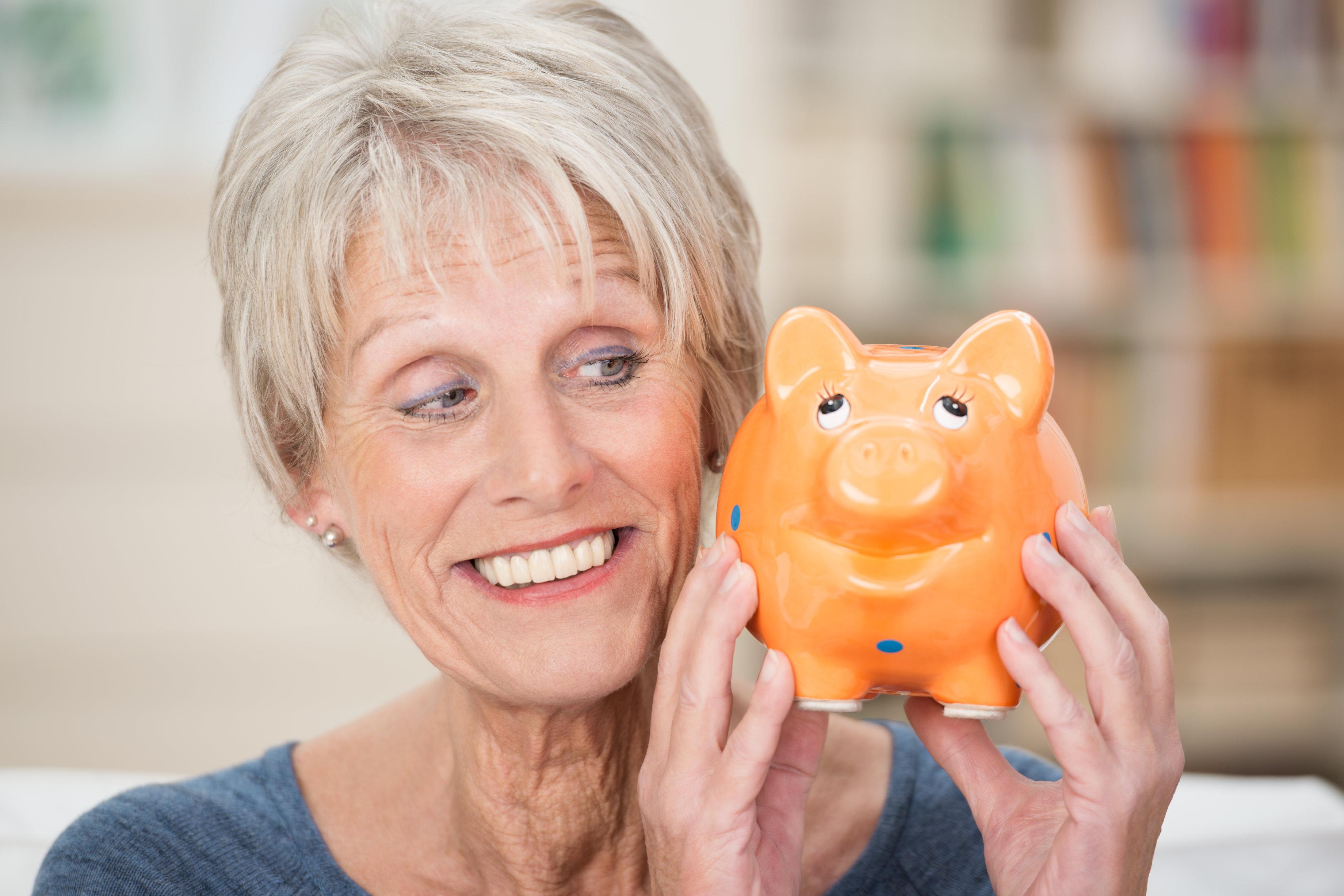 lchelnde ltere frau schaut auf sparschwein