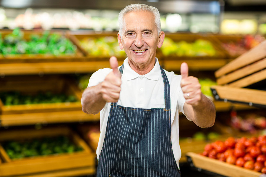 Senior worker showing thumbs ups in supermarket